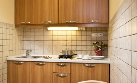felszerelt konyha: hűtőszekrény, tűzhely és edények